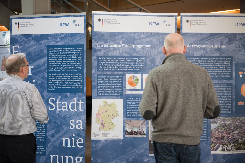 """Bild von einer Veranstaltung, bei der 2 Menschen sich die Wanderausstellung """"Energetische Stadtsanierung"""" ansehen"""