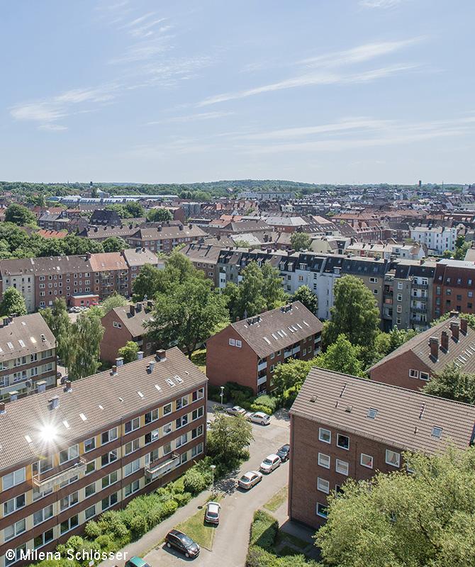 Vogelperspektive auf ein Wohngebiet mit Zeilenbauten. Im Hintergrund ist die restliche Stadt sichtbar.